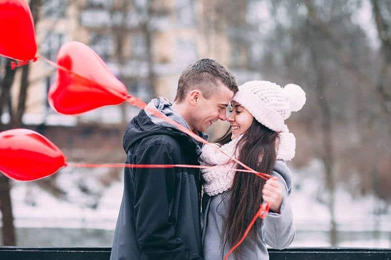 une femme tient un ballon en forme de cœur et embrasse un homme