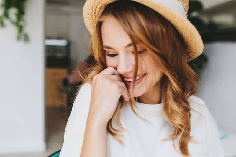 une fille timide et heureuse couvre son visage avec sa main
