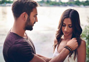 un homme touche les cheveux d'une femme au bord de l'eau