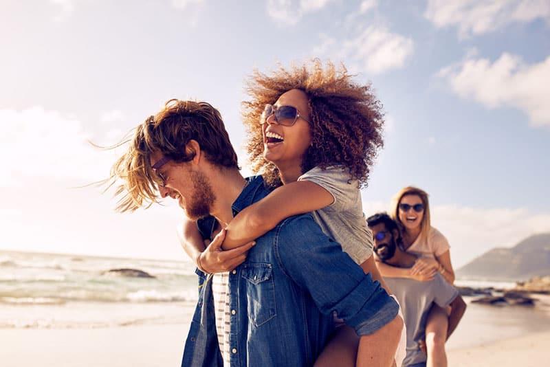 Groupe d'amis marchant le long de la plage, avec des hommes faisant du ferroutage pour les petites amies