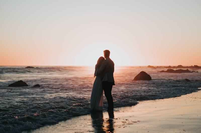photo de silhouette d'un couple se tenant sur la plage et regardant le coucher de soleil