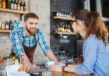 Barista souriante et jeune jolie femme à lunettes discutant dans un café
