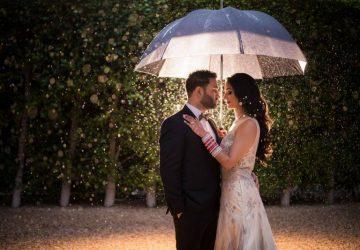 Le marié et la mariée sous un parapluie blanc pendant la nuit
