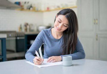 Une femme souriante écrit une lettre à la maison