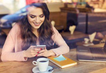 Une femme souriante envoie des SMS sur son téléphone au café