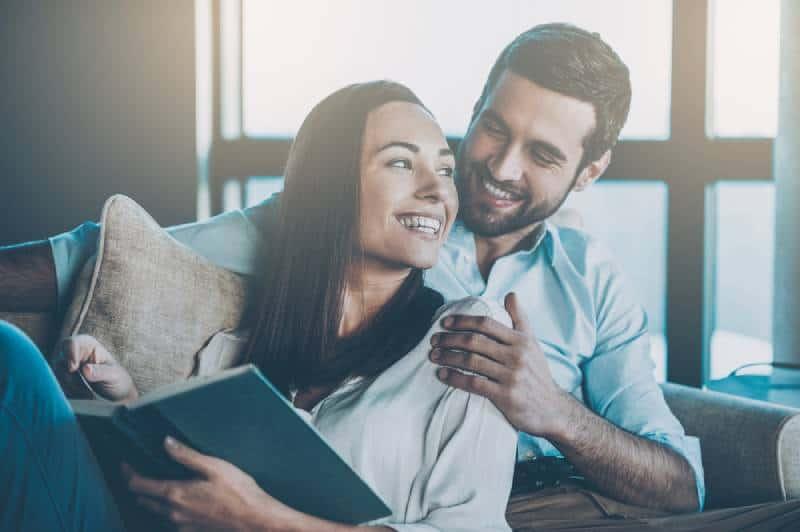 Un beau jeune couple amoureux qui se lie et sourit en tenant un livre dans les mains d'une femme