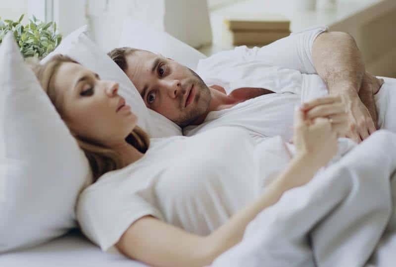 Un couple attentionné allongé sur le lit