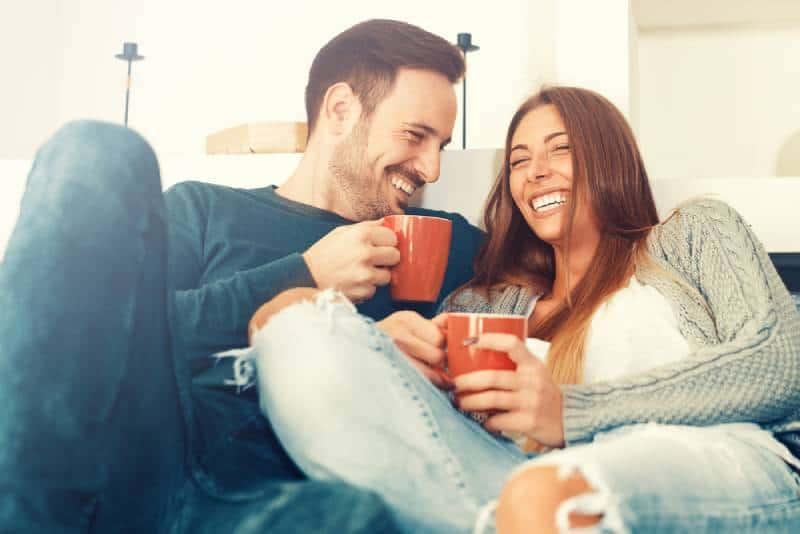 Un couple souriant assis dans le salon