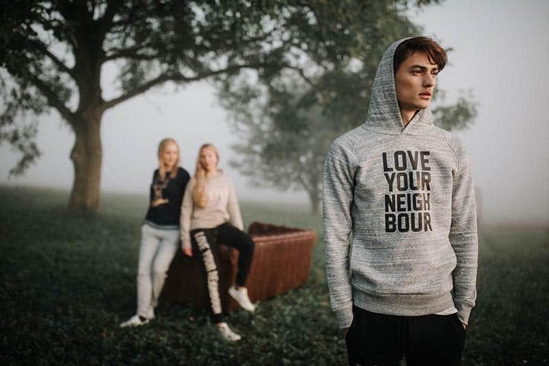 Un homme attentionné se tient devant deux amies à l'extérieur