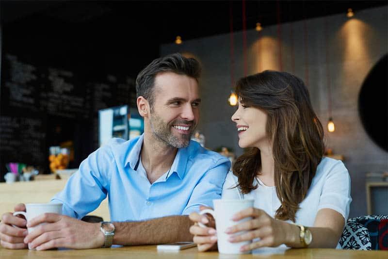Un homme et une femme souriants assis au café