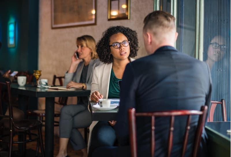 Une femme sérieuse parle à un homme dans un café