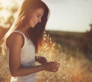 une femme se tient avec une fleur à la main