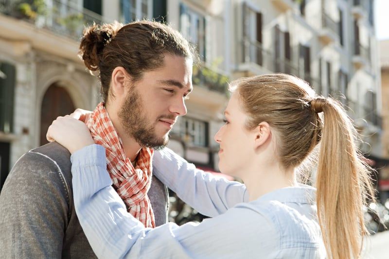 Vue de côté d'un couple souriant qui s'embrasse et se regarde à l'extérieur