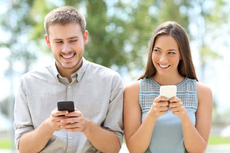 Vue de face d'un couple ou d'amis utilisant des smartphones et se regardant avec méfiance
