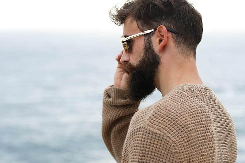 Vue latérale d'un homme barbu portant des lunettes de soleil et un sweat-shirt marron à l'extérieur