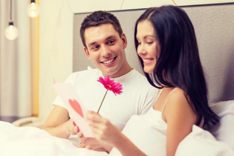 couple souriant au lit avec carte postale et fleur rose