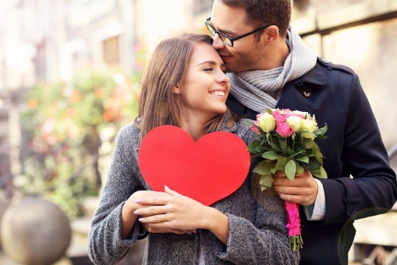 Photo de jeune couple avec fleurs et coeu