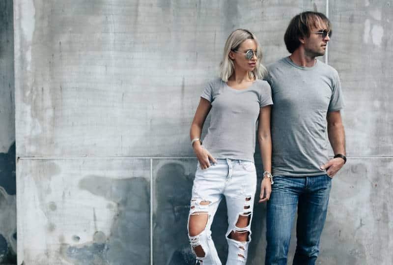 deux hipsters en t-shirt gris se tenant devant le mur