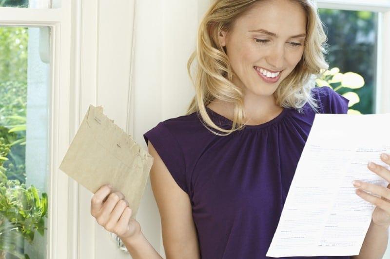 Heureuse jeune femme lisant une lettre à la maison
