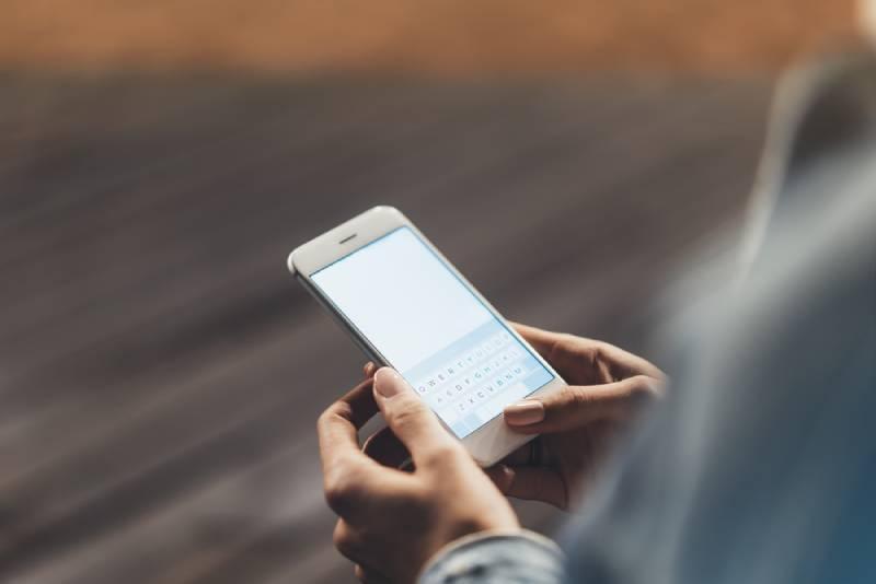 femme tenant son téléphone
