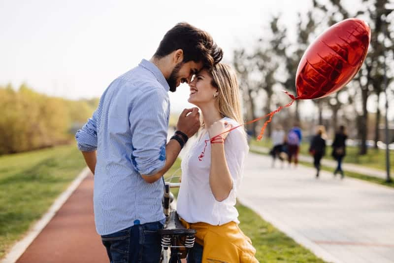 femme tenant un ballon en forme de coeur tout en regardant son petit ami