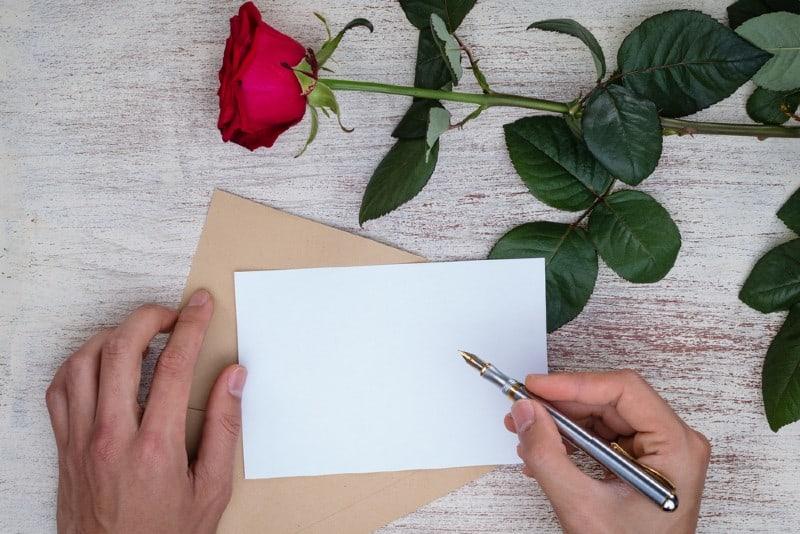händerna på en man som skriver ett kärleksbrev
