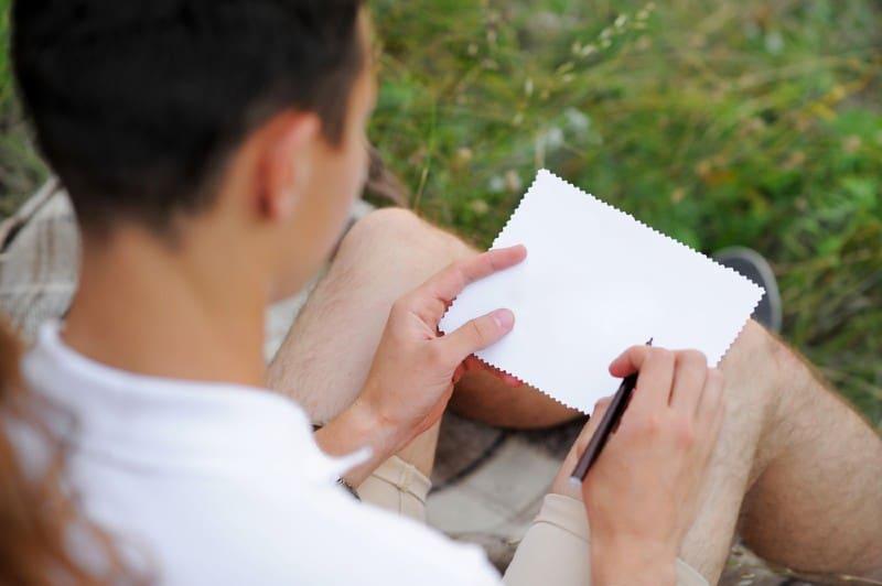 Un jeune homme écrit une lettre et tient une feuille de papier vierge sur ses genoux