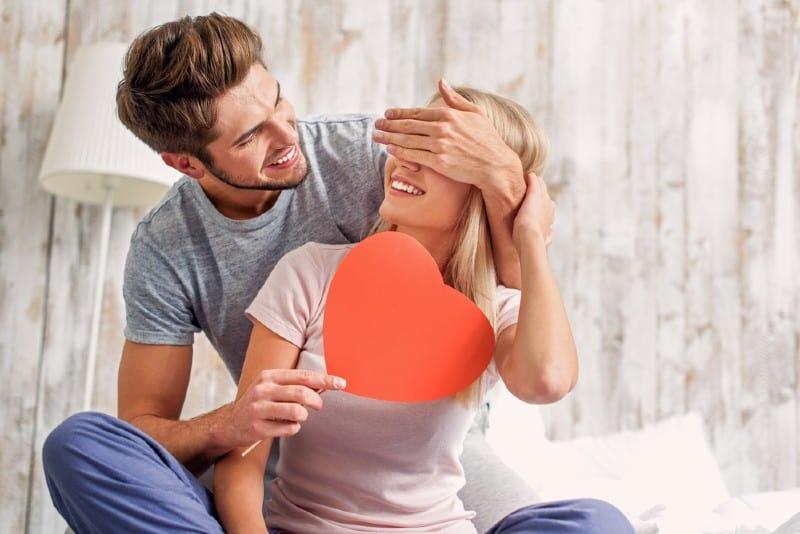 Heureux jeune homme couvrant les yeux des femmes avec surprise et lui donnant une carte coeur