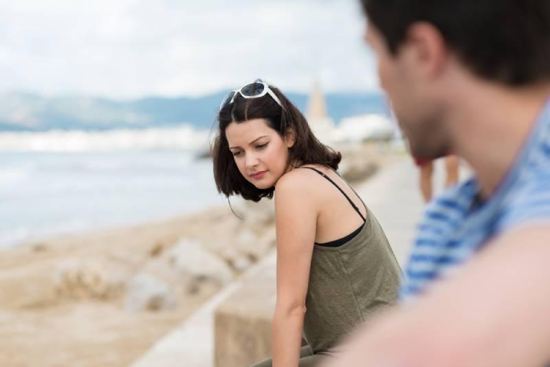 homme regardant une jeune femme à la plage
