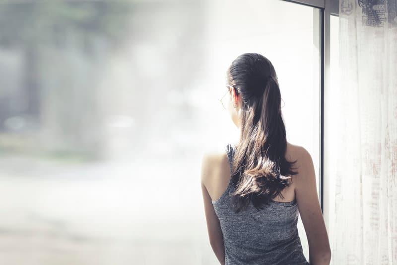 la femme regarde par la fenêtre