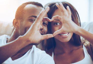 Beautiful young African couple sitting close to each other and looking through a heart shape made with their fingers 116/5000 Beau jeune couple africain assis près l'un de l'autre et regardant à travers une forme de coeur faite avec leurs doigts