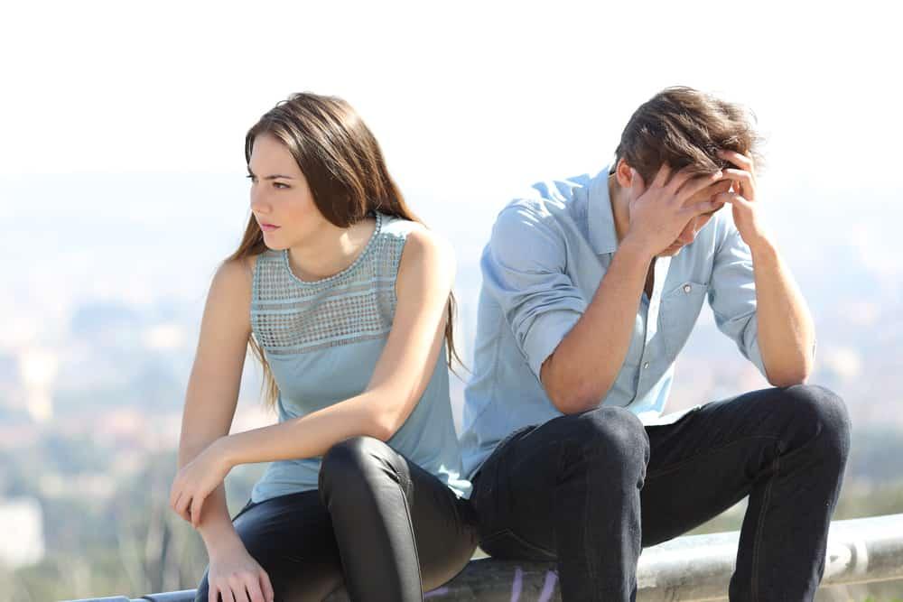 l'homme est assis à côté de la femme tenant sa tête