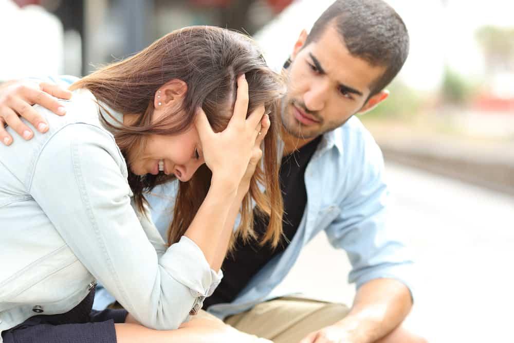 l'homme réconforte la femme alors qu'ils sont assis sur le banc et elle pleure