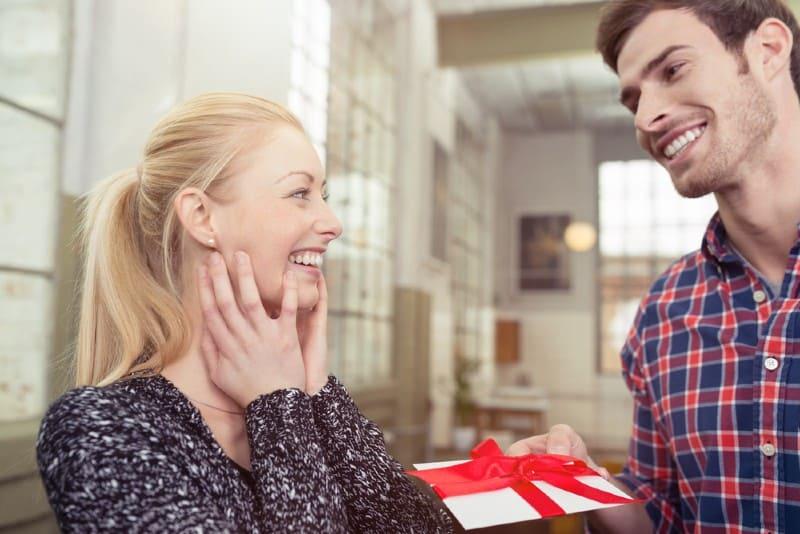 Beau mari souriant donnant à sa jolie jeune femme blonde une carte surprise