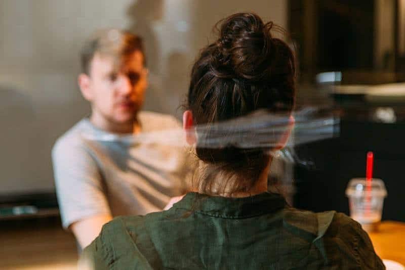 photo à faible profondeur de champ d'un homme et d'une femme discutant dans un café