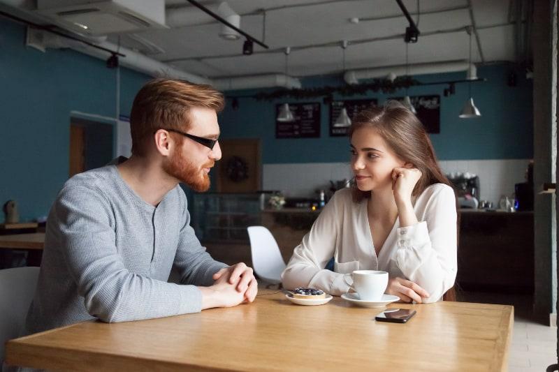 un homme et une femme se regardant et se parlant dans un café