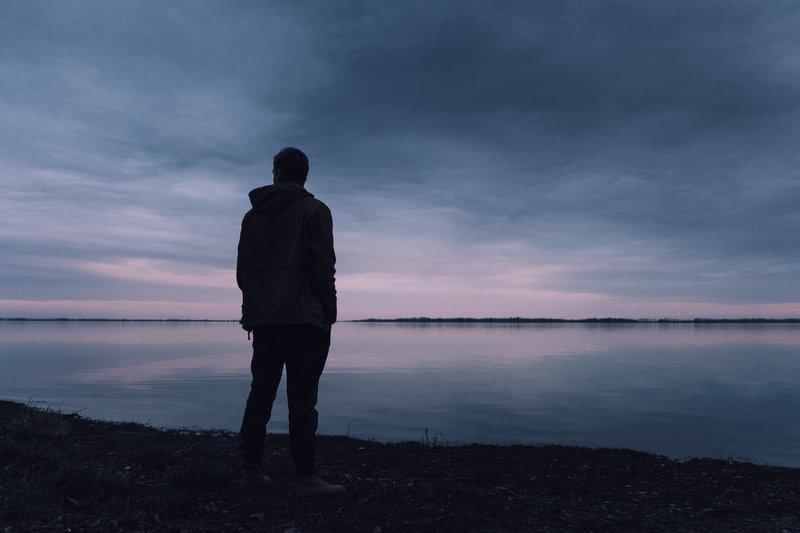 un homme se tient au bord de la rivière, le dos tourné