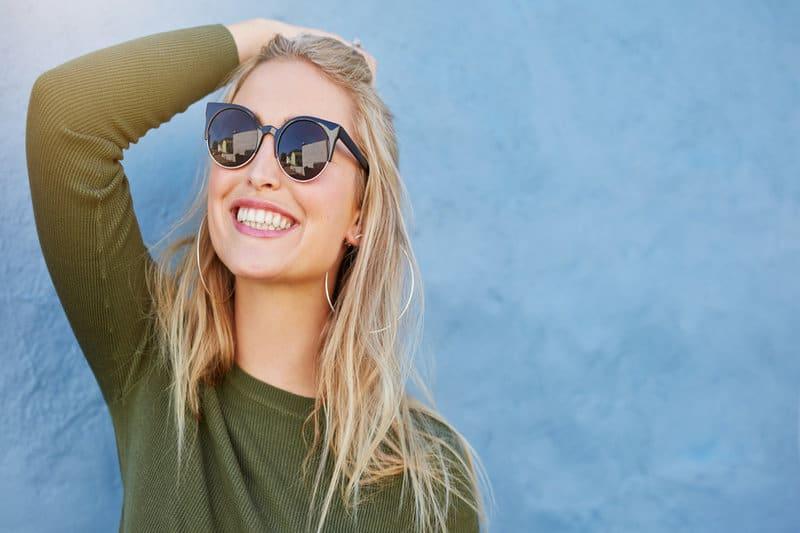 une femme avec des lunettes noires rit
