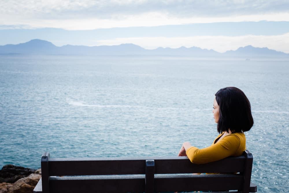 une femme noire est assise sur un banc et regarde au loin