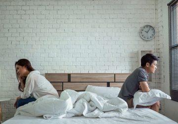 couple assis à l'écart sur le lit