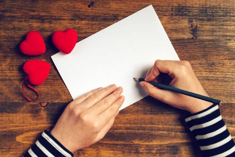 mains d'une femme écrivant une lettre d'amour