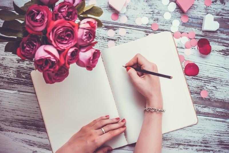 Mains féminines écrivant en cahier ouvert et bouquet de roses sur la vieille table en bois