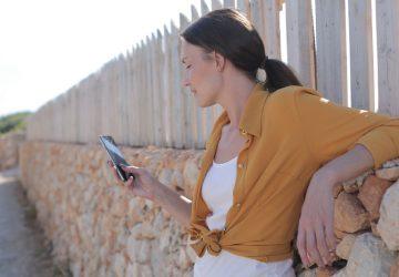 une femme aux cheveux noirs se tient avec un téléphone à la main