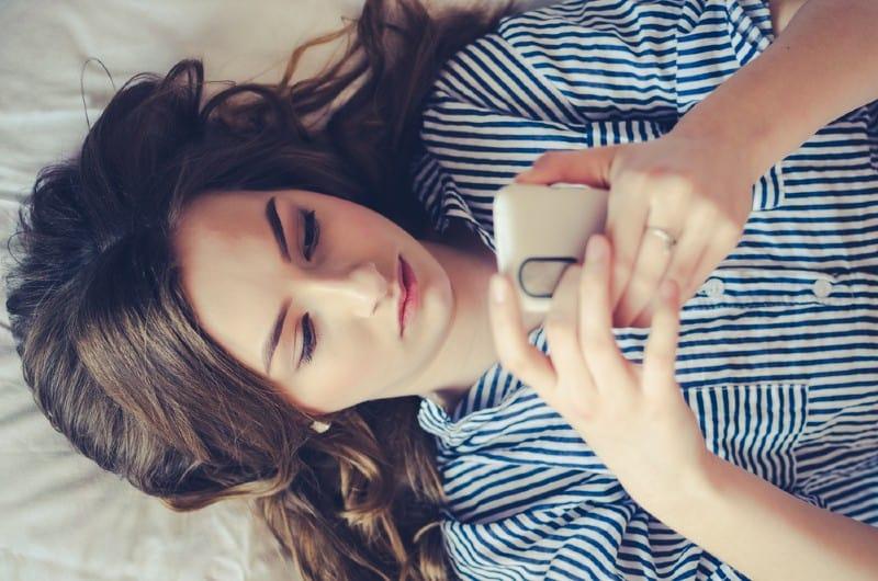 Gros plan d'une adolescente triste couchée dans son lit à l'aide de son mobile