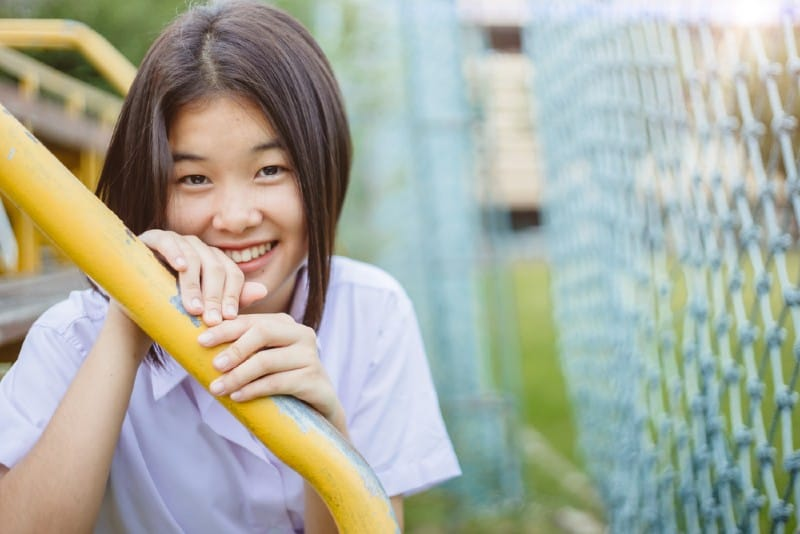 Adolescente timide asiatique souriant et regardant la caméra