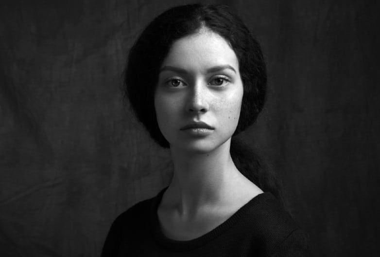 Portrait noir et blanc dramatique d'une belle fille solitaire avec des taches de rousseur isolé sur un fond sombre en studio shot