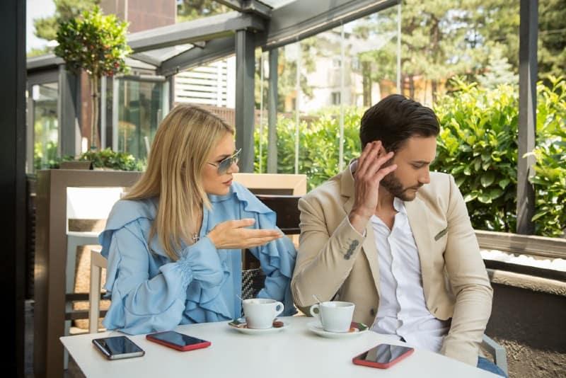 Un jeune couple ayant une dispute au jardin café restaurant