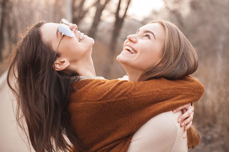 de jeunes amis heureux qui s'embrassent et lèvent les yeux