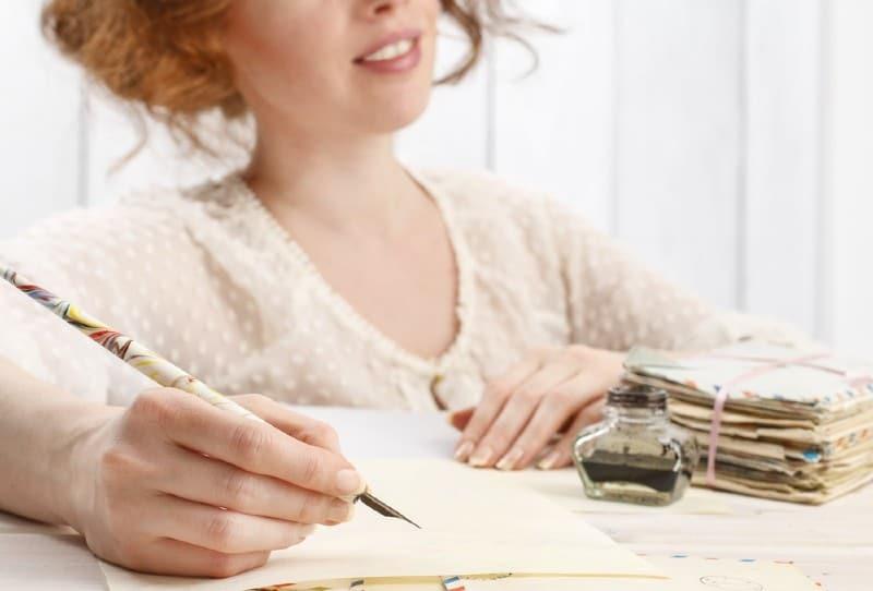 photo vintage d'une jeune femme écrivant une lettre