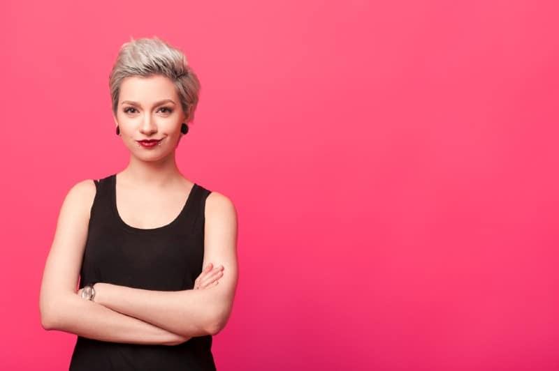Femme confiante debout avec les bras croisés isolé sur fond rose